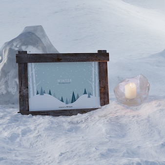 Frozen candle beside frame with winter theme