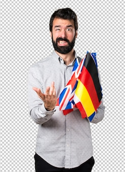 Frustrated handsome man with beard holding many flags