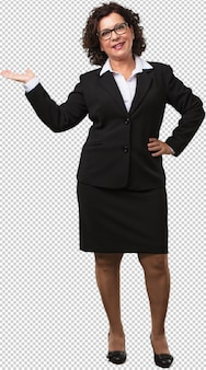 Full body middle age business woman holding something with hands, showing a product, smiling and cheerful, offering an imaginary object