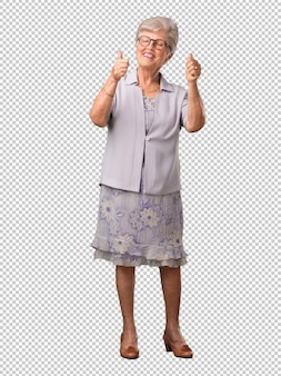 Full body senior woman cheerful and excited, smiling and raising her thumb up