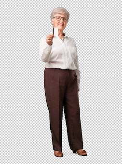 Full body senior woman cheerful and smiling, very excited holding the new bank card