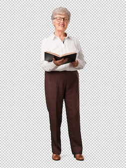 Full body senior woman concentrated and smiling, holding a textbook, studying to pass an exam or reading an interesting book