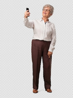 Full body senior woman confident and cheerful, taking a selfie, looking at the mobile with a funny and carefree gesture, surfing the social networks and internet