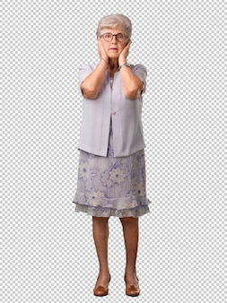 Full body senior woman covering ears with hands, angry and tired of hearing some sound