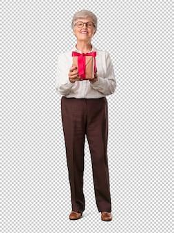 Полное тело старшей женщины, счастливой и улыбающейся, держащей хороший подарок, взволнованной и полной, празднующей день рождения или показанное событие