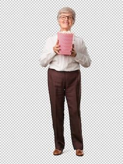 Full body senior woman happy and fascinated, holding a striped popcorn bucket, surprised by the new movie, eyes open and expression of admiration Premium Psd
