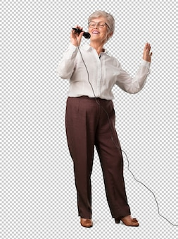 Full body senior woman happy and motivated, singing a song with a microphone, presenting an event or having a party, enjoy the moment