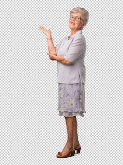 Full body senior woman holding something with hands, showing a product, smiling and cheerful, offering an imaginary object