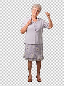 Full body senior woman listening to music, dancing and having fun, moving, shouting and expressing happiness, freedom concept