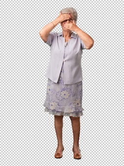 Full body senior woman looking through a gap, hiding and squinting