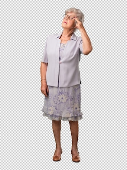 Full body senior woman making a suicide gesture, feeling sad forming a gun with fingers