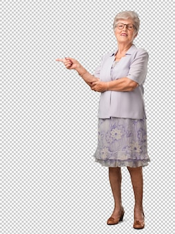 Full body senior woman pointing to the side, smiling surprised presenting something, natural and casual