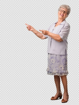 Full body senior woman pointing to the side, smiling surprised presenting something