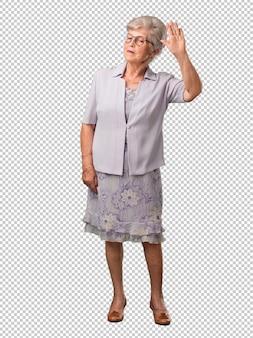 Полное тело старшие женщины серьезные и решительные, положить руку впереди, остановить жест, отрицать концепцию