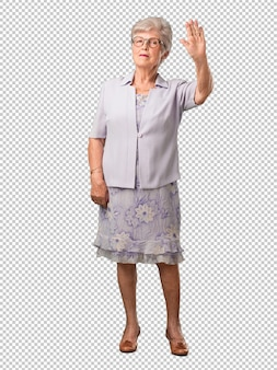 Full body senior woman serious and determined, putting hand in front, stop gesture, deny concept