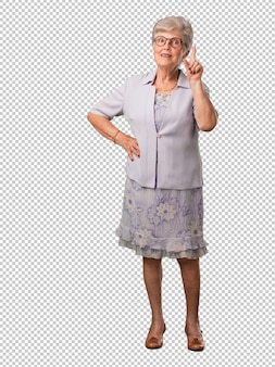 Full body senior woman showing number one, symbol of counting, concept of mathematics, confident and cheerful
