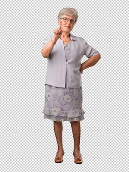 Full body senior woman showing number one, symbol of counting