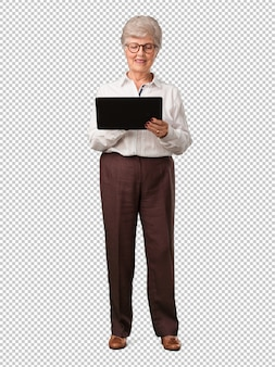 Full body senior woman smiling and confident, holding a tablet, using it to surf the internet and see social media, communication concept