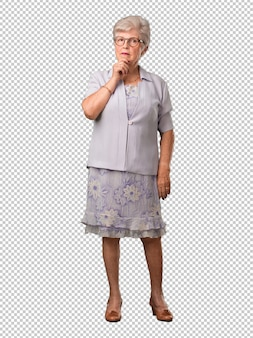 Full body senior woman thinking and looking up, confused about an idea