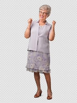 Full body senior woman very happy and excited, raising arms