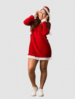 Full body young santa curvy woman covering ears with hands