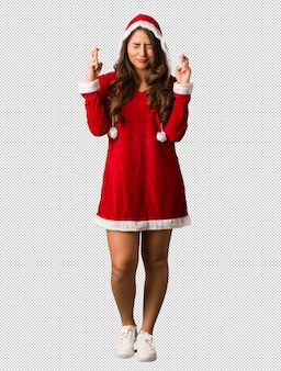 Full body young santa curvy woman crossing fingers for having luck