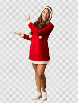 Full body young santa curvy woman holding something with hand