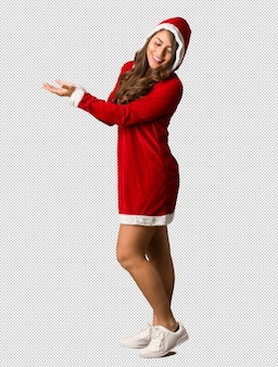 Full body young santa curvy woman holding something with hands