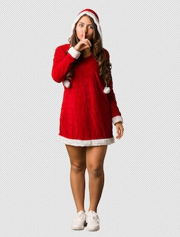 Full body young santa curvy woman keeping a secret or asking for silence