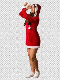 Full body young santa curvy woman making the gesture of a spyglass