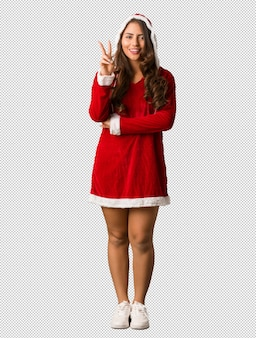 Full body young santa curvy woman showing number two