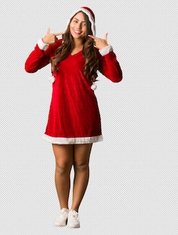 Full body young santa curvy woman smiles, pointing mouth