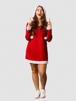 Full body young santa curvy woman surprised pointing up to show something