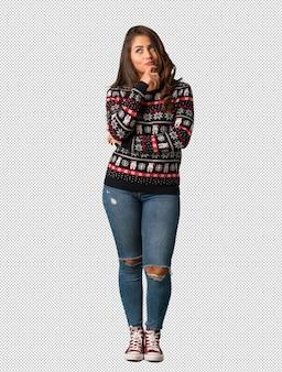 全身の若い女性がクリスマスジャージーを身に着け、疑問と混乱