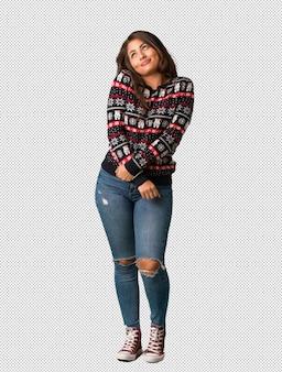 Полная молодая женщина в ношении рождественского трикотажа мечтает о достижении целей и задач