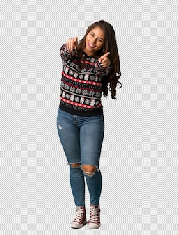 Full body young woman wearing a christmas jersey cheerful and smiling
