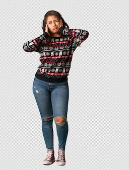 Full body young woman wearing a christmas jersey covering ears with hands