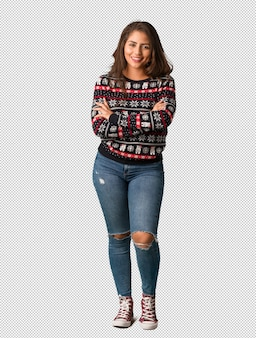 Full body young woman wearing a christmas jersey crossing arms, smiling and relaxed