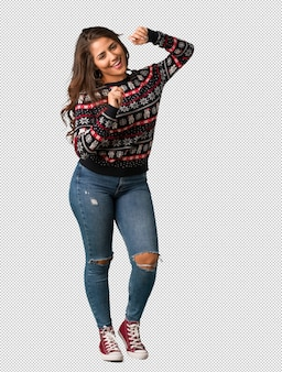 Full body young woman wearing a christmas jersey dancing and having fun