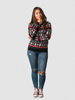 Full body young woman wearing a christmas jersey doubting and confused