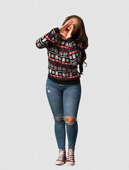 Full body young woman wearing a christmas jersey shouting something happy to the front