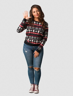 Full body young woman wearing a christmas jersey showing number five
