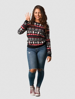 Full body young woman wearing a christmas jersey showing number four