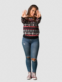 Full body young woman wearing a christmas jersey showing number ten