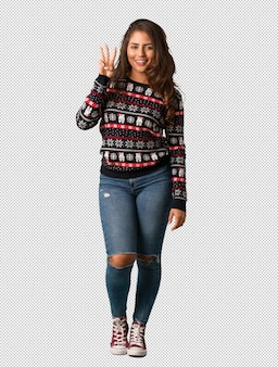 Full body young woman wearing a christmas jersey showing number three
