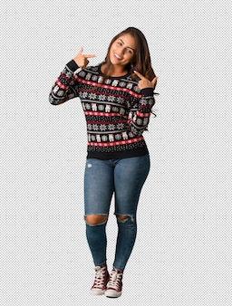 Full body young woman wearing a christmas jersey smiles, pointing mouth