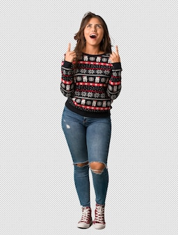 Full body young woman wearing a christmas jersey surprised pointing up to show something