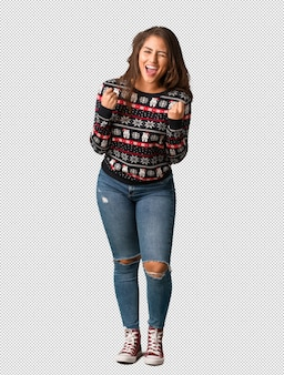 Full body young woman wearing a christmas jersey surprised and shocked