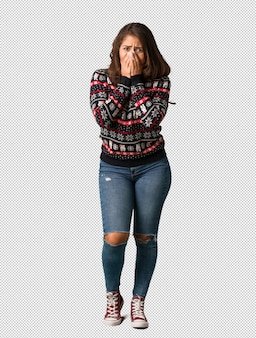 Full body young woman wearing a christmas jersey very scared and afraid hidden