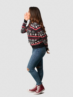 Full body young woman wearing a christmas jersey whispering gossip undertone